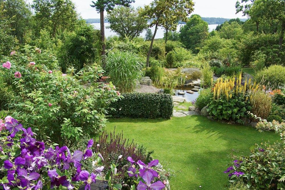 Uppifrån det stora trädäcket är utsikten magnifik. Med Mälarens glittrande vatten som fond breder makarna Wåhlins vackra samlarträdgård ut sig över den svagt sluttande söderslänten.