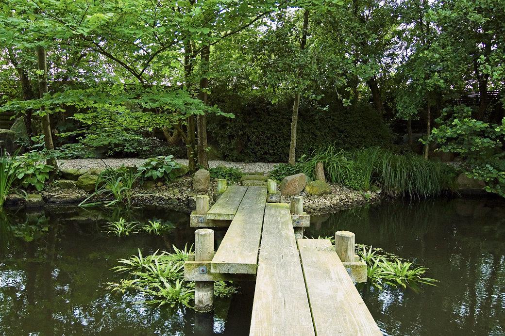 En enkel och vacker japanskinspirerad bro byggd av plankor ger en suggestiv och exotisk känsla. I Hviids Have ansluter bron till en trädinfattad gångväg runt dammen. Kring flyter vattenhyacinter. Bakom buskaget och planket på andra sidan bron breder det fynska jordbrukslandskapet ut sig.
