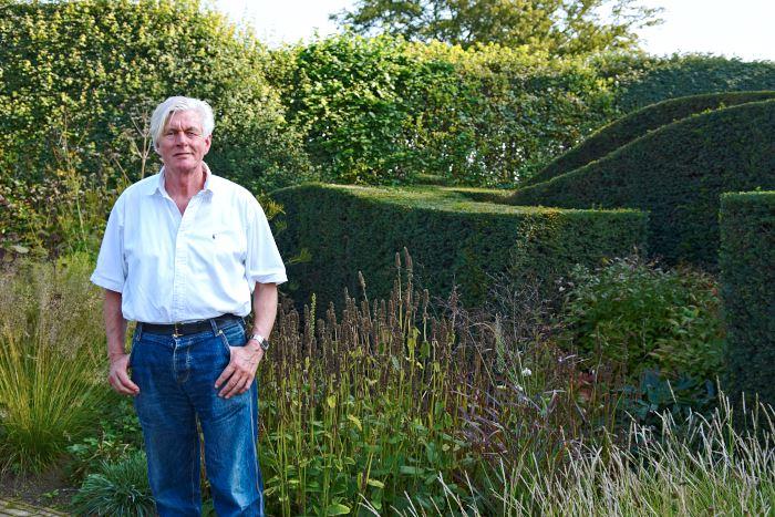 Piet Oudolf längs ner i sin trädgård framför de formklippta idegranshäckarna.