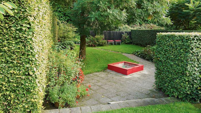 Den läckra sandlådan i rött är en del av det här trädgårdarummets helhet, dess färg speglas effektfullt i blommorna och stolarnas sittdynor. Bild från Mien Ruys trädgårdar i Holland.