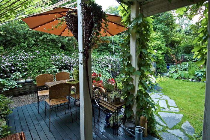 Den här inbjudande utblicken möts man av när man öppnar dörren mot trädgården hemma hos makarna Söderlund på Pilgården i Sundsvall. När det regnar kan man slå sig ner i en skön korgstol i det skyddade rummet mellan ute och inne som skapats under det utbyggda trätaket.