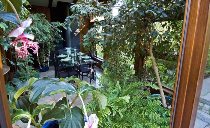 Vad är inne och vad är ute? I Villa Fraxinus flyter matsalen med de storväxta krukväxterna ihop med trädgården utanför. Generösa fönsterpartier, ett golv i marknivå och stenbeläggning med liknande utseende inomhus och ute skapar den goda integrationen.