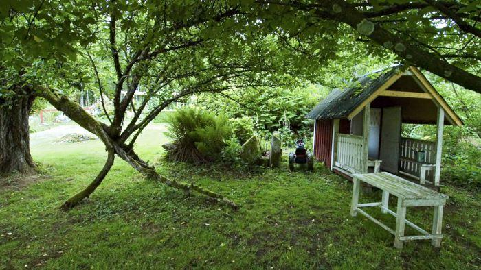 Lekstugan ligger lagom gömd under under träden i Drömmens trädgård. Invid finns en alldeles magisk port att krypa igenom.