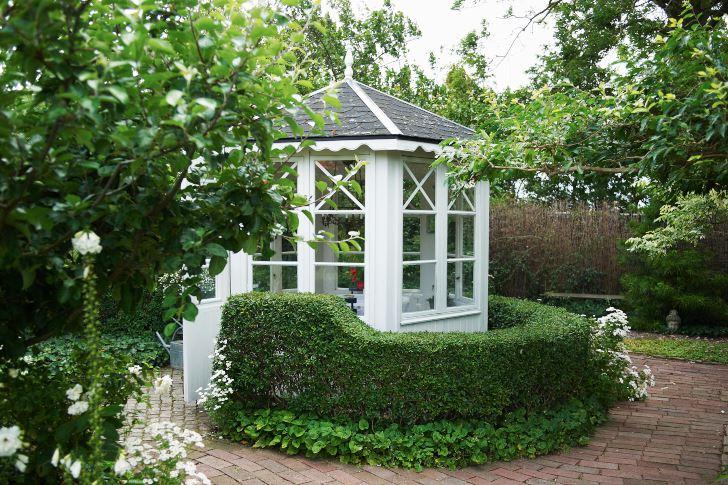 Lusthuset köpte de färdigt, men med tiden har Per bytt ut det mesta. Buxbomshäcken skapar en grön ram som ger byggnaden bättre samhörighet med trädgården.