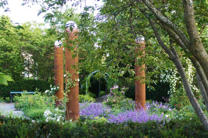 I juli fylls rosenträdgården av dofter från rosor och aromatiska perenner som salvia, kantnepeta, stenkyndel och isop. Längs skulpturpelarna klänger klätterrosor med glest växtsätt. Ett medvetet val för att de inte ska ta udden av ljusspelet som när de klotrunda lamporna i toppen tänds mörka kvällar.
