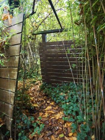 Plank kan användas för att avgränsa inte bara yttre tomtgräns utan också för att åtskilja olika delar inom trädgården. Vad döljer sig bakom hörnet, är en fråga som man alltid ställer sig inför en passage av det slag som Per Friberg skapat mellan det lummiga woodlandet och tomtens, delvis, formella framsida.