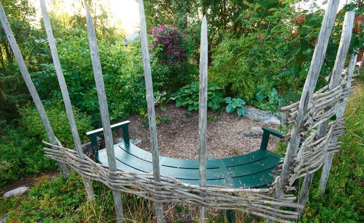 I kanten av skogen placerade Maud Persson i Hälsingland en av trädgårdens bänkar med utsikt över prunkande funkior, klättrande klematis och graciös bergbambu. Till ryggstöd flätad pil.
