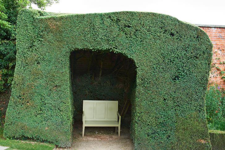 Buxbomen omsluter soffan likt en grotta på Powis Castle i Wales. Fullt görligt också i Sverige, men för att slippa vänta i årtionden är idegran att föredra. Å den andra sidan är glädjen att se hur det växer en av de saker som särskiljer inredning utomhus mot inne. En viss skicklighet med häcksaxen behövs också.
