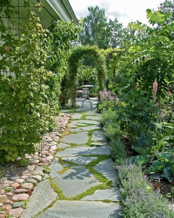 Oregelbundna skifferplattor mjukar upp den raka trädgårdsgången hemma hos Wåhlins i Skokloster.