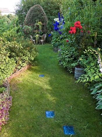 En halvhydda av flätad pil avslutar den engelska gången hos makarna Söderlund i Sundsvall. Rabatternas vindlande form och blocken av turkosblå glasbetong får blicken att löpa från sida till sida vilket visuellt breddar den långsmala terrassen.
