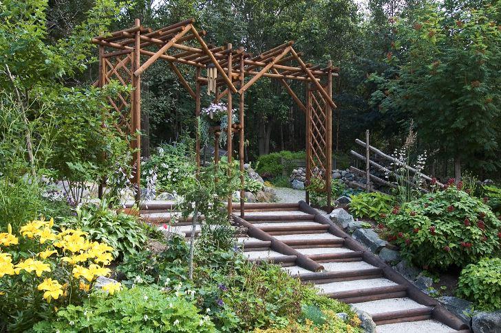 En stilig trappa i asiatisk stil underlättar passagen mellan två höjdnivåer i Margareta Borgströms trädgård i Hortlax i Norrbotten. En egenhändigt snickrad dubbelportal markerar trappans början på den övre nivån samtidigt som den ger trappan mycket av dess speciella karaktär.