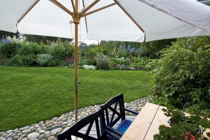 I Cathrine Öhlunds trädgård utanför Piteå ramas utsikten ut mot rabatterna in av parasollet. Uteplatsen, ett mjukt, rundat trädäck lagt i marknivån, kantas av en vindlande kullerstenskant. Ett förskönande inslag som dessutom inte är bredare än att man kan kliva över det om man tycker att det är knepigt att gå över de kullriga stenarna.