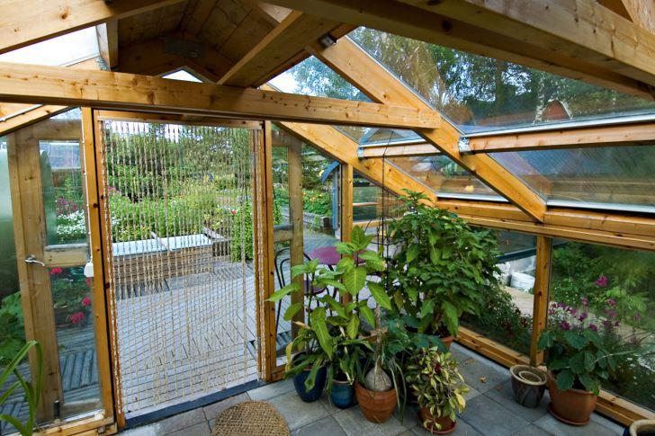 Inifrån växthuset ser man ut över köksträdgården med de upphöjda odlingsbäddarna och det vackert lagda trägolvet som Kurt Ove gjort.
