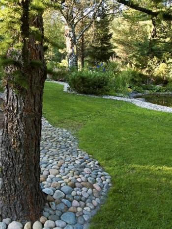 De mjukt böljande kullerstensytorna ger karaktär och struktur. Längst till höger syns en del av trädgårdsdammen som inramas av perenner med vackra blad och blommor.