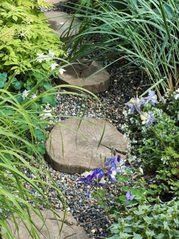Ett bra alternativ för trädgårdens mindre gångar är trampstenar lagda i ett lager av grus. Att använda träkubbar som material i gångar är inte helt lämpligt, de blir hala och ruttnar snabbt om de inte är impregnerade. I det här fallet är därför träkubbarna gjorda av betong. Gruset är dansk sjösten. Växterna som hänger ut över gången förstärker den informella karaktären. Bild från vår idéträdgård på Ulriksdal Flower Show 2004.
