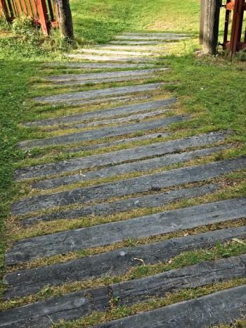 Horisontella linjer skapar en upplevelse av ökad bredd. Något så enkelt som långsmala trampbrädor i gräsmattan kan bidra till att trädgårdsrummet känns bredare. Bild från Träslottet i Arbrå, Hälsingland.