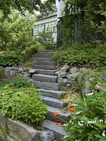 En diagonalt dragen trappa, som här hemma hos Anna-Lena Wibom på Lidingö, är ett praktiskt och klädsamt alternativ för den branta sluttningen där en rak trappa inte förmår ta upp hela lutningen på ett gångvänligt sätt. Stilen passar speciellt mindre trappor, som inte har alltför stor bredd. Med växter som väller in över trappan från sidorna mjukas intrycket upp samtidigt som trappstegskanterna döljs.