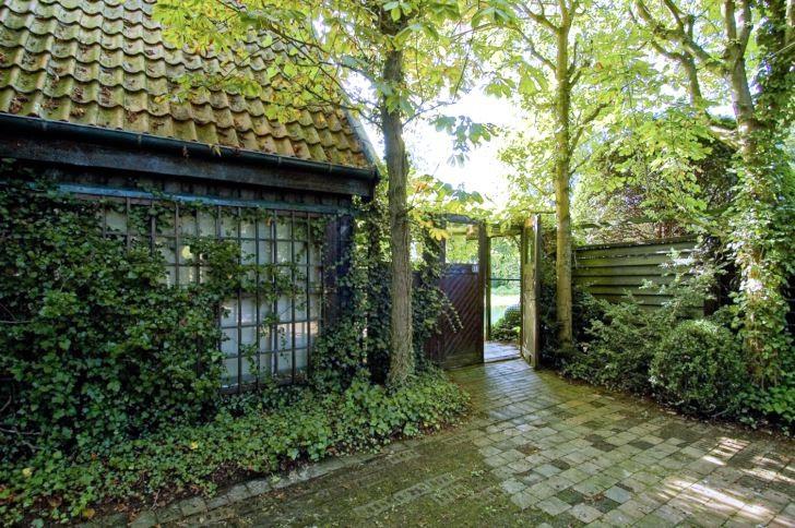 Ett behagligt ljus skapas under kastanjernas kronor vid entrén till Per Fribergs hus i Bjärred. Städsegröna växter som murgröna och buxbom tillsammans med variationer i stenbeläggningen skapar intressanta mönster även under den avlövade årstiden. Glimten av trädgården innanför, genom fönstren och den öppna dörren, bidrar till att väcka besökarens nyfikenhet och lust.