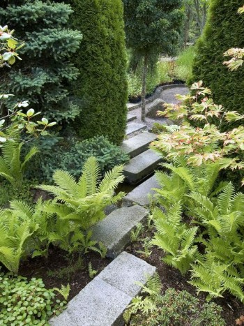 Diagonalt förskjutna stenblock skapar en spännande passage mellan två trädgårdsrum. Tillsammans med växterna skapar läggningsmönstret en informell atmosfär. Bild från Skovtroldens planteskole på Själland i Danmark.