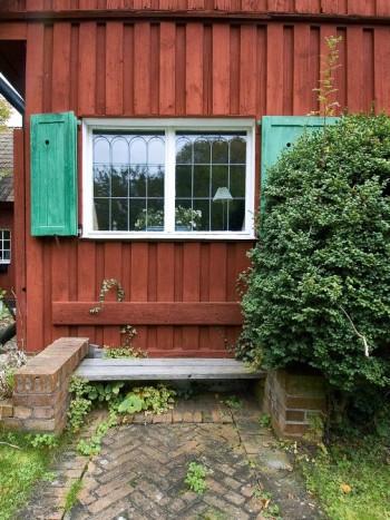 En bänk in mot husväggen tar minimalt med plats och blir tidigt varm om våren. Med omgivande tegelmurar, som här i Emma Lundbergs (1869–1953) trädgård på Lidingö, får man fina avställningsytor för kaffekoppen och frukostsmörgåsen.