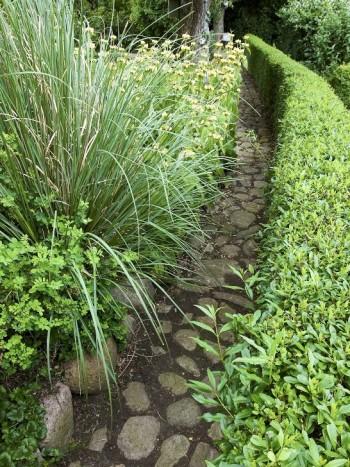 En smal, svagt böjd gång av kullersten i bar jord kantad av en smal ligusterhäck på den ena sidan och rabatter på den andra är vackert och skapar spänning genom att vägen framför döljs. Från Eva och Per Juul-Jensens trädgård på Langeland i Danmark.