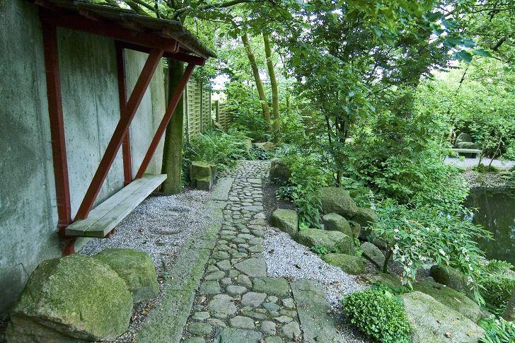 En enkel träbänk med eget tak har monterats direkt på betongmuren i Hviids japanska trädgård på Fyn i Danmark. De rödmålade träbjälkarna, som bär upp bänkens tak, kontrasterar fint mot betongens blekgrå färg. När man slår sig ner ser man ut över en stor japaninspirerad damm med vackra broar, öar och paviljonger. Tack vare den skyddande muren i ryggen är man innesluten i trädgårdens egna magiska värld och helt avskärmad från jordbrukslandskapet som ligger på andra sidan