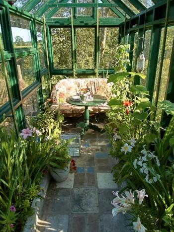 Ett växthus som avslappnat uterum. Med en bekväm soffa insmugen bland frodiga växter är det skönt att dra sig tillbaka när det är för regnigt eller kyligt för att sitta ute. Bilden hemifrån konstnären Maria Björklund på Österlen.