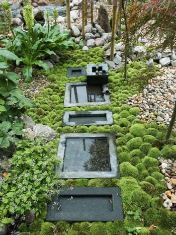 Rektangulära fågelbad på rad skapar en sakral känsla i den japanska delen av makarna Söderlunds trädgård i Sundsvall. De omgivande japanska lönnarna återspeglas i de stilla små vattenytorna. Med en mörk botten skapas fina reflexioner.