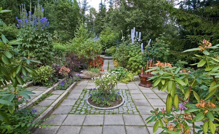 I ett av de många små trädgårdsrummen som finns bredvid den långa entrégången hittar man rododendron och riddarsporrar tillsammans med ettårsblommor som tagetes, begonior, fuchsior och margueriter.