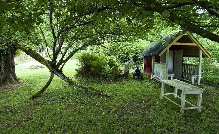 Lekstugan ligger lite lagom undangömd under träden och invid den finns en magisk port man kan gå under. Drömmens trädgård.