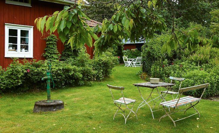Enklast tänkbara uteplats är några bord och stolar i gräsmattan, gärna under ett fruktträds krona. Ingenting hindrar att man placerar ut flera stycken i trädgården. Bild från Drömmens trädgård i Småland, Katarina och Sten Dunérs sommarparadis.