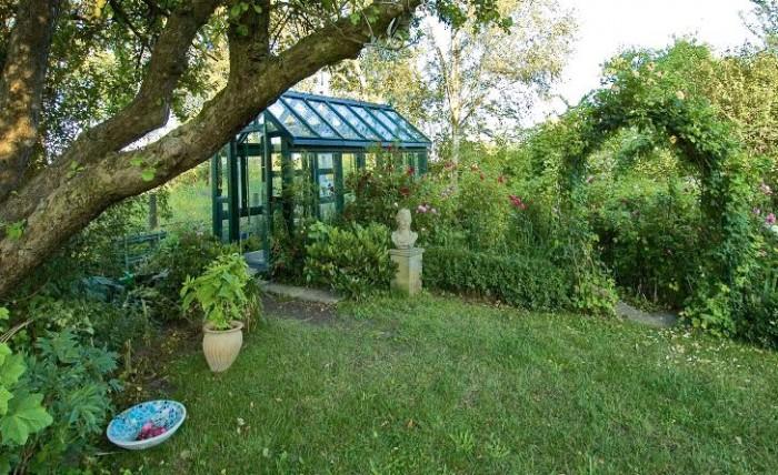 Det kombinerade växt- och lusthuset invid rosengården hemma hos konstnären Maria Björklund.