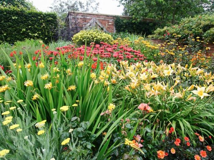 Varma känslor: röllika, montbretia, daglilja och röd temynta i Wollerton Old Hall Garden, Shropshire, England.