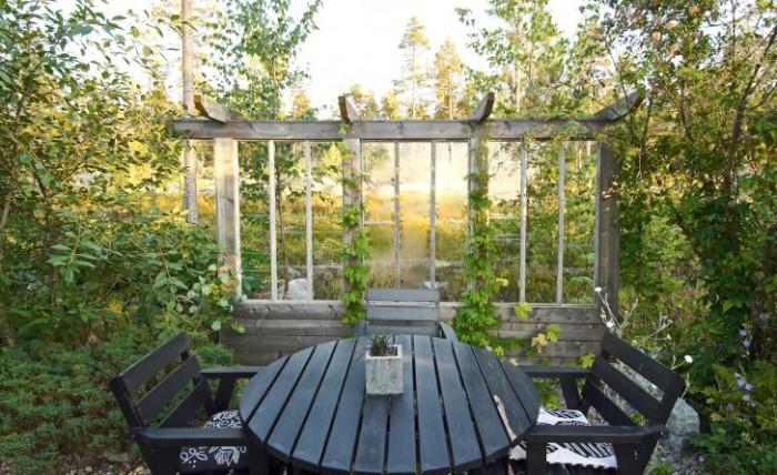 Med glasfönster mot tallskogsslänten skapas en nästan magisk känsla på sittplatsen i utkanten av makarna Perssons trädgård. Fönsterväggen ramar in och förstärker effekten av den vackra utsikten samtidigt som den skapar lä. På sensommarkvällen gör den höga luftfuktigheten glaset immigt.