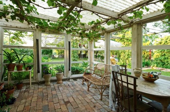 Uterummet är avslappnat charmigt med enkla möbler, frodiga växter och golv av återanvänt tegel från en riven gård i närheten. I taket klänger en vindruvsranka som bjuder på söta gröna druvor fram på hösten.
