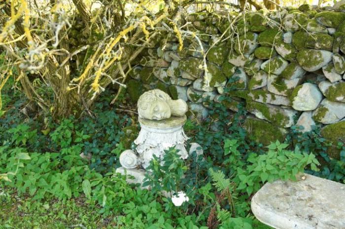 Med hjälp av överbliven teaterrekvisita, en mossbeklädd stengärdsgård och vildväxande örter och bladväxter har ett charmigt litet trädgårdsrum som för tankarna till antikens Grekland skapats.