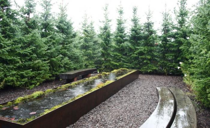Vid skogstjärnens mörka vatten ska man begrunda människans öde. I stiliserad form finns den i Skogens trädgård. De gråaktiga barren på den smalväxande serbiska granen, Picea omorica, bidrar till mystiken. Att det regnar är bara som sig bör.