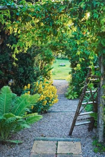 Växtportaler och den långa raka trädgårdsgången förstärker den fria siktlinjen mot brunnen.