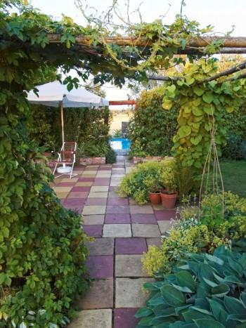 Trädgårdsgången med en cirkelrund simbassäng i den i ena änden.