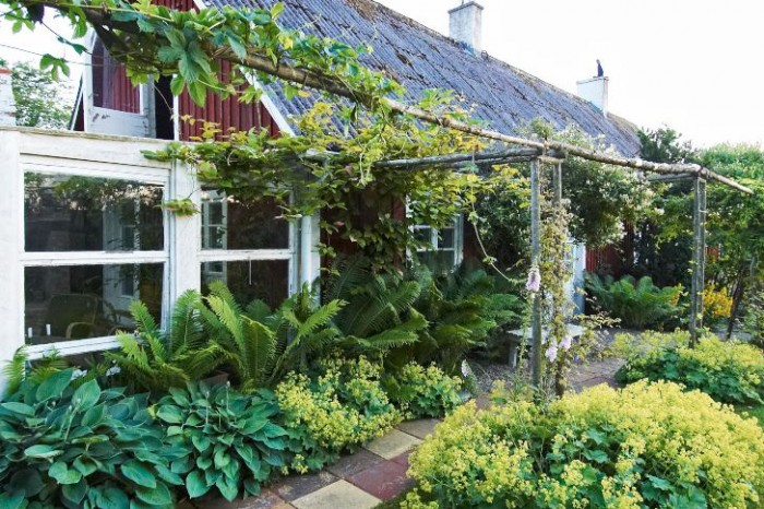 Runt uterummet på husets östra gavel är miljön överdådigt lummig och rofylld.