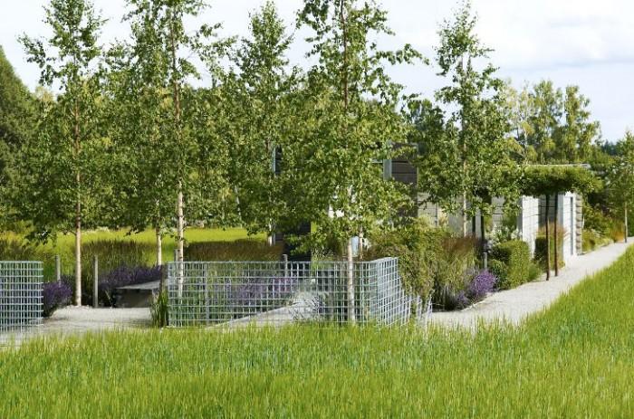 Omgivet av sädesfält, här korn på väg mot mognad, står Ulf Nordfjells skapelse Skogens trädgård.