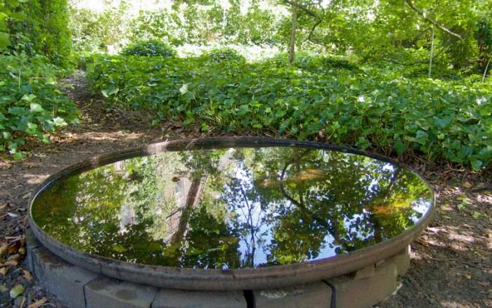 På smala stigar kommer vi in i ett halvdunkelt trädgårdsrum med ett stort grunt vattenfat på marken. Tack vare en mörk botten reflekteras grenverk och hus. Marken mellan växterna är täckt av murgröna, Hedera helix, som håller sig lika grön och fin året om.