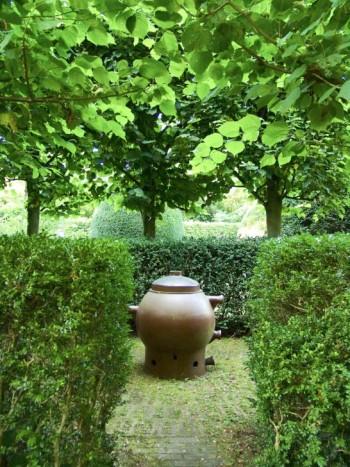 En keramikform som använts för industriellt bruk vid Höganäsfabriken omges av klippta buxbomshäckar och tuktade lindar i ett alldeles eget litet trädgårdsrum som man passerar på väg in till huset. En lika enkel som formskön komposition.