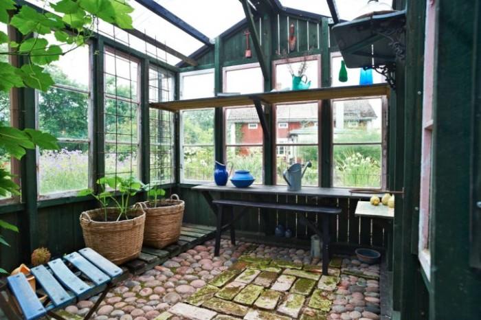 Inifrån växthuset, byggt av Seppo, ser man ut mot stugan, det är från den fönstren kommer. Brädorna står glest, och på vintern blåser det tvärs igenom. På sommaren däremot blir klimatet perfekt. Under våren är här fullbelamrat av småplantor.