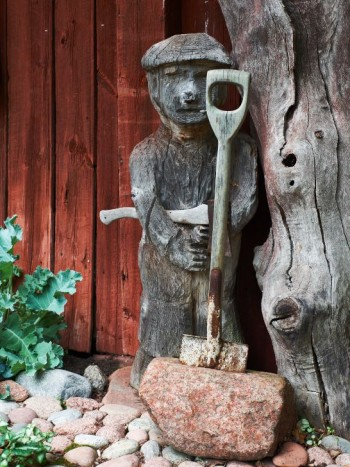 Det var Tittes svärfar från Karelen som tillverkade gubben invid bagarstugan. Spaden i stenen står Titte för. Installationen kallar hon Perkele, ett av de få finska ord som de flesta svenskar kan.