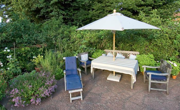 Med rosor, schersminer, fleråriga kryddväxter och rosengeranium och pelergoner i krukor skapas en ombonad känsla runt uteplatsen i Lilla Toscanas trädgård utanför Kalmar.