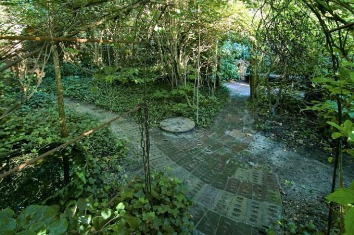På smala gångar lagda med skorstenstegel går vi genom fantasifulla växttunnlar inte långt från själva boningshuset. I ryggen har vi rosengården och rakt fram ett litet slutet trädgårdsrum med en bänk att slå sig ner på vid sidan om stora rododendronbuskar. Gången till vänster leder oss vidare till den spännande passagen mellan två plank.