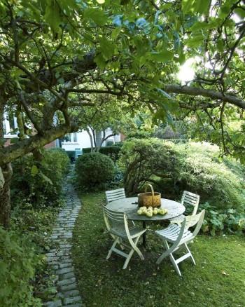 Under det knotiga gamla äppelträdets nästan horisontella grenar, i Bauers trädgård på Lidingö, skapas en tydlig takkänsla. Här står en trivsam trädgårdsmöbel för avkopplande vilostunder, middagar eller avställning av äppelkorgen under arbetet med fruktskörden. När man passerar den lägsta grenen på den lilla stenlagda gången till vänster får man böja sig ner på samma sätt som när man går genom dörröppningar i gamla hus, vilket skapar en hemtrevlig känsla av uppvuxen genuin trädgård.