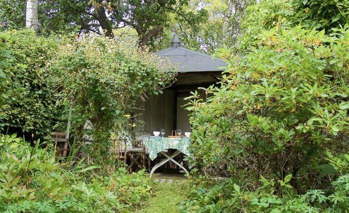 I Bauers radhusträdgård på Lidingö skapas ett effektivt insynsskydd av en tak- och väggförsedd uteplats som byggts i ett av tomtens hörn. Ett sånt här bygge ger en omedelbar förbättring av trädgårdens privathet samtidigt som man får en trevlig sittplats som går att använda även när regnet strilar ner. För att göra det behövs i Sverige i allmänhet byggnadstillstånd och medgivande av grannar.