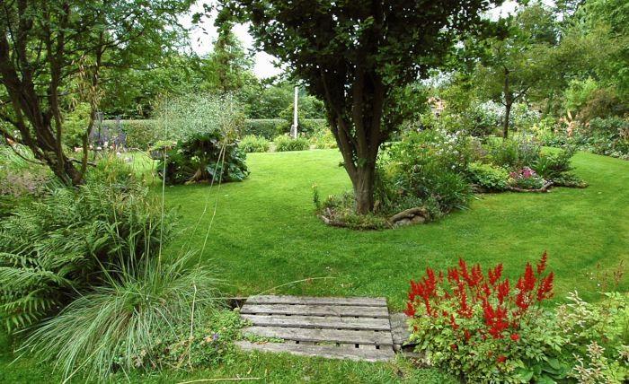 Allt som ger variation är effektivt för att trolla bort platthet. En liten träbrygga som bryter av gräsmattan för att ta oss över en riktig bäck, eller bara något som ger illusionen av att vara ett vattendrag, skapar spänning och liv. Bilden är från familjen Gosvigs trädgård på Fyn i Danmark.